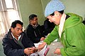 The Polling Officer administering indelible ink to the finger of a female voter at a polling booth in '15 miles', Tsomgo (Changu) lake, Sikkim during the third phase of General Election-2009 on April, 30, 2009.jpg