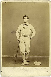 A baseball player is standing, facing the camera, with the top of a baseball bat in his right hand, and the bottom resting on the ground