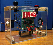 A simple digital timer. The internal components—including the circuit board with control chip and LED display, a battery, and a buzzer—are visible.