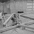 Timmerman in de kampong bezig met de bouw van een huis, Bestanddeelnr 255-6717.jpg