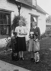 Two lady golfers with golf clubs and trophies, Builth Wells