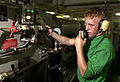 US Navy 030813-N-6213R-017 Aviation Boatswain's Mate Airman Danny Donahoe adjusts the tension of arresting gear machinery under the flight deck aboard USS John C. Stennis (CVN 74).jpg