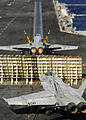 US Navy 050214-N-4166B-100 An F-A-18C Hornet, launches as another F-A-18 Hornet prepares for launch on the flight deck aboard the Nimitz-class aircraft carrier USS Abraham Lincoln (CVN 72).jpg