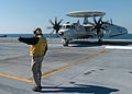 US Navy 051027-N-9174G-006 An E-2C Hawkeye, assigned to the Bluetails of Carrier Airborne Early Warning Squadron One Two One (VAW-121), is directed on the flight deck.jpg