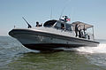 US Navy 060510-N-5330L-132 A Sailor assigned to Inshore Boat Unit Four One (IBU-41) assigned to Naval Coastal Warfare Squadron Four (NCWS-4) waves as his boat speeds.jpg