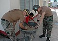 US Navy 060614-N-3931M-007 A local boy assists two U.S. Navy Seabees from Naval Mobile Construction Battalion Four Zero (NMCB-40) remove foreign debris from cement mix.jpg