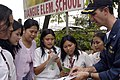 US Navy 070213-N-9604C-149 USS Blue Ridge (LCC 19) Commanding Officer, Capt. Jeff Bartkoski, writes his name for a group of student reporters at Tiangue Elementary School in Lapu-Lapu City during a community service project.jpg