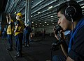 US Navy 070405-N-2659P-112 Sailors from Deck Department aboard the Nimitz-class aircraft carrier USS John C. Stennis (CVN 74) use sound-powered phones and hand signals to assist in bringing over supplies during a replenishment.jpg