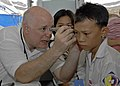 US Navy 070720-N-4954I-048 Dr. Dana Braner, part of the non-governmental organization Project Hope, examines a Vietnamese patient's ear at the Man Thai Ward Medical Station in support of Pacific Partnership 2007.jpg