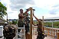 US Navy 071004-N-7092S-099 Utilitiesman 2nd Class Craig Gardner and Builder 2nd Class William Lathan, Seabees attached to Military Sealift Command hospital ship USNS Comfort (T-AH 20), build a gazebo at the Zanderij Clinic.jpg