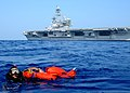 US Navy 100615-N-7908T-868 Search and rescue swimmer Logistics Specialist 2nd Class Wellington G. Bookert swims with Oscarto a rigid-hull inflatable boat during a man overboard recovery drill.jpg