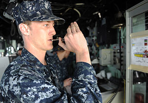 US Navy 111231-N-EK905-067 Boatswains Mate 3rd Class Trevor Mink uses a boatswain's pipe on the bridge to signal early chow aboard the amphibious a.jpg