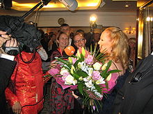 Ursula Andress in front of a crowd of people; a boom microphone is above her head