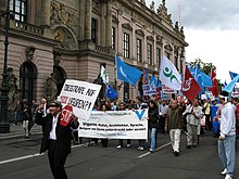 Street demonstration with banners, passing an official building