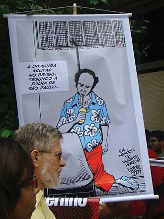 "Folha de S.Paulo - Protest against the usage of the term. The banner, a cartoon by Carlos Latuff, sarcastically adds a glass and straw to the famous photo of Vladimir Herzog hanged after torture, with the implication that the Folha de S.Paulo is trying to whitewash the realities of the dictatorship that killed him in 1975. It says: ""The military dictatorship in Brazil according to Folha de S.Paulo""."