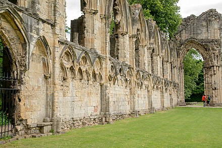 A portion of the ruins of St Mary's Abbey, York, founded in 1155, extensively damaged by fire in 1157, rebuilt by 1294 and destroyed during the Dissolution in the 16th century Wall of the ruins, st marys abbey York 8714.jpg