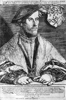 A  middle aged man, Wilhelm, Duke of Jülich-Cleves-Berg, is sitting at a table. He is  dressed in a soft cap that falls to the side of his head. He is wearing  fur-trimmed  robes, and nestled in the edges of the robes is a chain, with a cross  at its nadir. His hands are folded on the table before him. He is  wearing several rings, and one hand holds a pair of gloves. The family  crest hangs on the chair behind him.