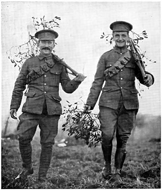 British Army uniform and equipment in World War I - British soldiers wearing the service dress hat, and 1902 Pattern service dress. The ammunition bandolier would suggest these men are from an Infantry unit. As was common practice within the BEF, they have given their uniform badges to local well wishers, who early in the war greeted the arriving Tommies with olive leaves indicative of victory and peace. The missing badge's shadow on the NCO's forage cap looks like a Harp, and so  he may be from the Royal Irish Regt. whose regimental badge was the harp and crown. His companion could be a trooper due to the jodhpurs cut of his trousers, and the riding boots. Perhaps two brothers meeting up at an assembly point.