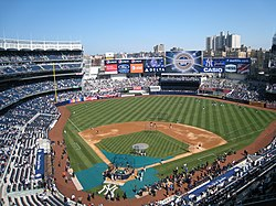 A baseball stadium with blue seats and buildings visible in the background. c746dc172