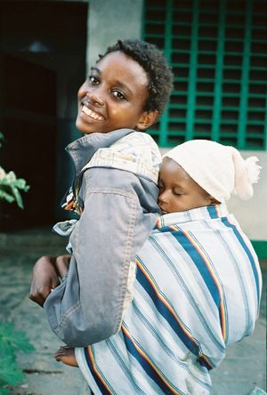 Baby sling - A young African woman carrying child in a baby sling.