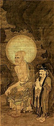 Painting of a tall, older man sitting, with an earring. His head is surrounded by an aura, and there is a short bearded man, wearing a headpiece, standing next to him.