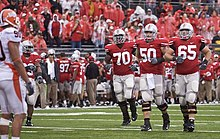 Three football players in red and grey uniforms approach the line of scrimmage.