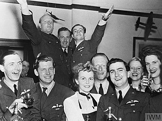 No. 92 Squadron RAF - Officers and guests celebrating the first anniversary of the arrival of No. 92 Squadron RAF at RAF Biggin Hill, September 1941.The group includes, in the front row, (left to right): Wing Commander John A. Kent (Kentowski), Flight Lieutenant Anthony Bartley, Mrs Wade, Flight Lieutenant Robert Holland, Pilot Officer Trevor Wade and two unidentified ladies. And in the back - Pilot Officer Sebastian Maitland-Thompson, Flying Officer Tom Weiss (Intelligence Officer) and Flying Officer Geoffrey Wellum.