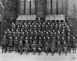 A large group portrait of men in military uniform. The men in the front row are seated, while six successive rows are standing behind them on elevated platforms. The men are standing in front of a large building with stained glass windows.