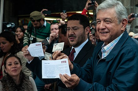Lopez Obrador (right) holding his Voter ID upside down along with Marti Batres (center) after submitting the formal political registration of MORENA to the INE AMLO se afilia a MORENA en el Zocalo (8361522287).jpg
