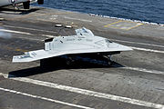 A U.S. Navy X-47B Unmanned Combat Air System makes an arrested landing aboard the aircraft carrier USS George H.W. Bush (CVN 77) as the ship conducts flight operations in the Atlantic Ocean off the coast of Vir 130710-N-LE576-002