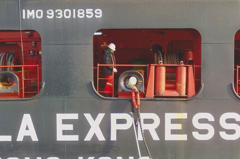 A crew member from the container ship takes the stern rope