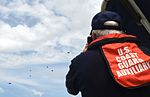 A member of the U.S. Coast Guard Auxiliary watches as members of the 181st Weather Flight parachute out of a C-130 Hercules.jpg