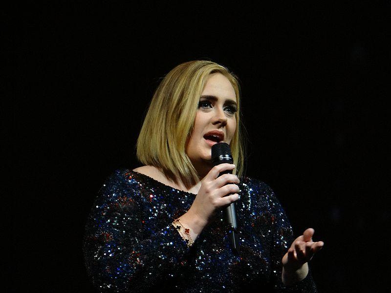 Cantora Adele segurando microfone enquanto canta. Passou por tratamento com Hipnose.