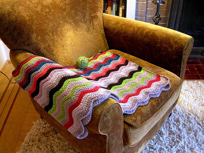 An Afghan blanket (in progress) on a chair. Fr...