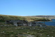 A cluster of ruined industrial buildings sits on the shore of a green, treeless landscape.