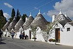 Small white houses with conic roofs.