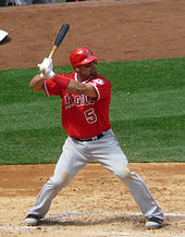 A brown-skinned man in a red baseball jersey and while pants takes a right-handed baseball batting stance.