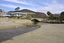 A creek flows out of a gap through a coastal mountain range and flows onto the beach.