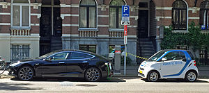 Plug-in electric vehicles in the Netherlands - Two electric cars charging on street in Amsterdam: Tesla Model S (left) and Smart ED (right).