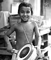 An Indian child playing a drum, music of India.jpg