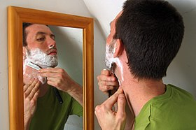 A man shaving using a straight razor.