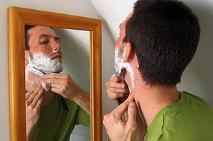 Shaving - A man shaving his neck using a shavette.