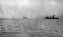 A line of four ships underway: the rightmost ship is the closest to the camera, while the leftmost ship is very distant. A landmass stretches along the horizon, behind the ships.