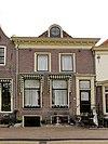 foto van Pand met voordeuromlijsting en eenvoudige lijstgevel met zware geprofileerde lijst met blokjes rond dakvenster