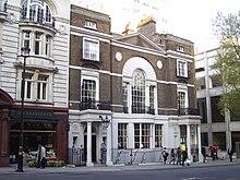 la fachada de un edificio georgiano de tres pisos en Londres.  El edificio es de ladrillo marrón rojizo, con bordes, pórtico y columnas de piedra Portland de color crema.