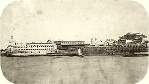 Photograph depicting a waterfront with stone quays, a paved ramp leading down to the water's edge, a fortress on the left edge of the picture, and spires, domes and multi-story buildings in the background