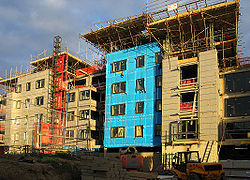 Building construction for several apartment blocks. The blue material is insulation cladding, which will be covered later.