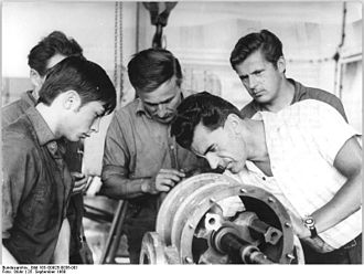 Master craftsman - A master discusses a vacuum compressor with his apprentice boy and several other craftsmen