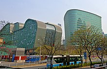 Two irregularly shaped greenish glass-faced buildings rise over a street lined with freshly budding trees on which a blue and white trolleybus is stopped