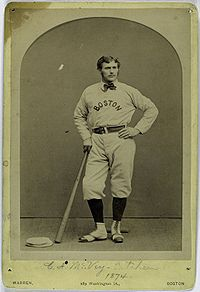 "A man, wearing a baseball uniform with the words ""BOSTON"" in the center, leans on a bat held in his right hand."